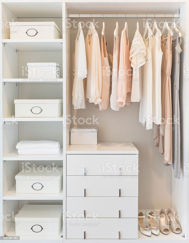white wardrobe on wooden floor with dress stock photo