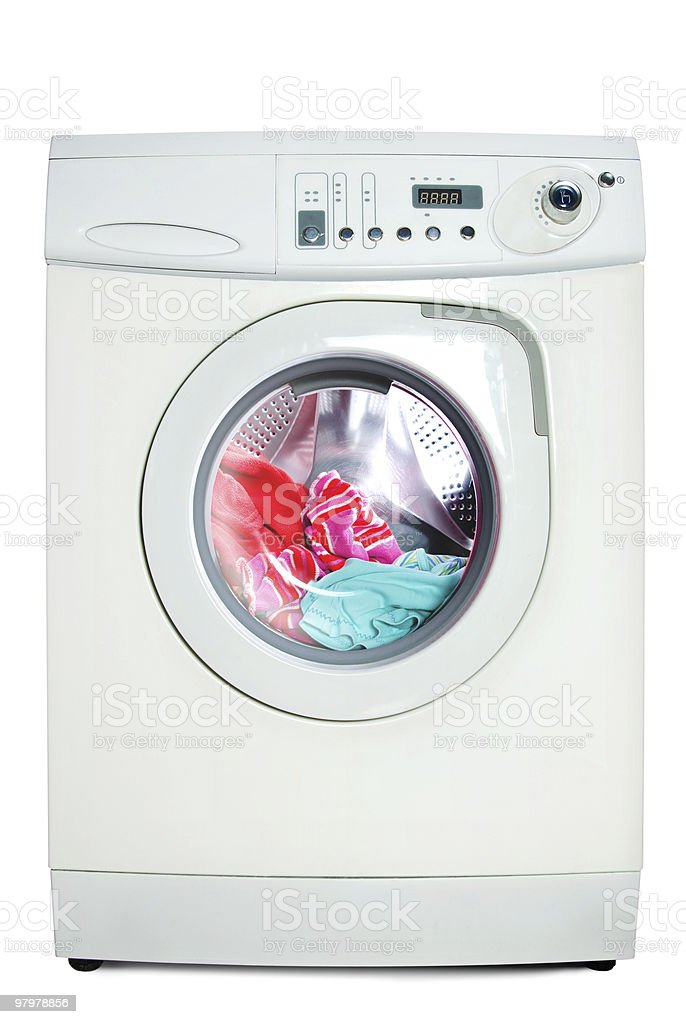 White washing machine with brightly colored clothing inside stock photo