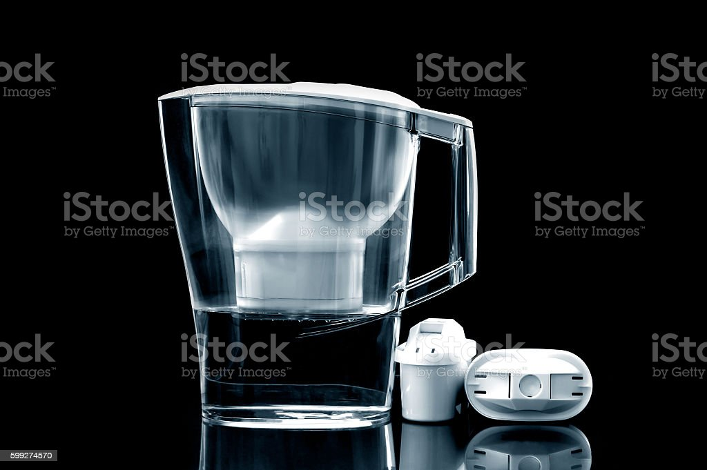 White water filter jug with spare filters on black background. stock photo