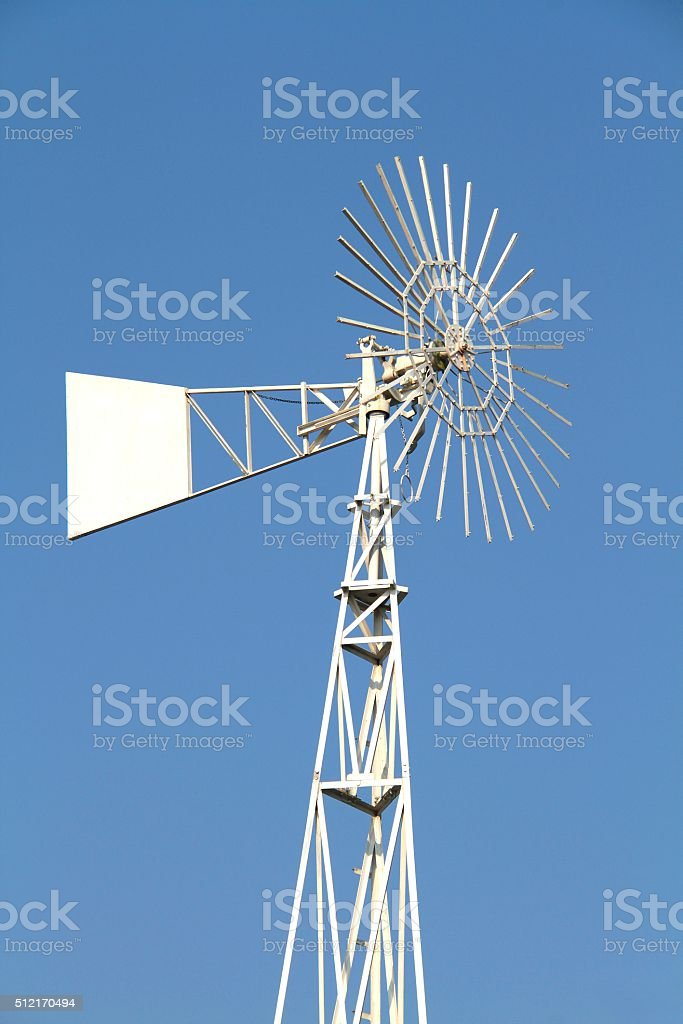 White water pumping wind mill on blue sky background stock photo