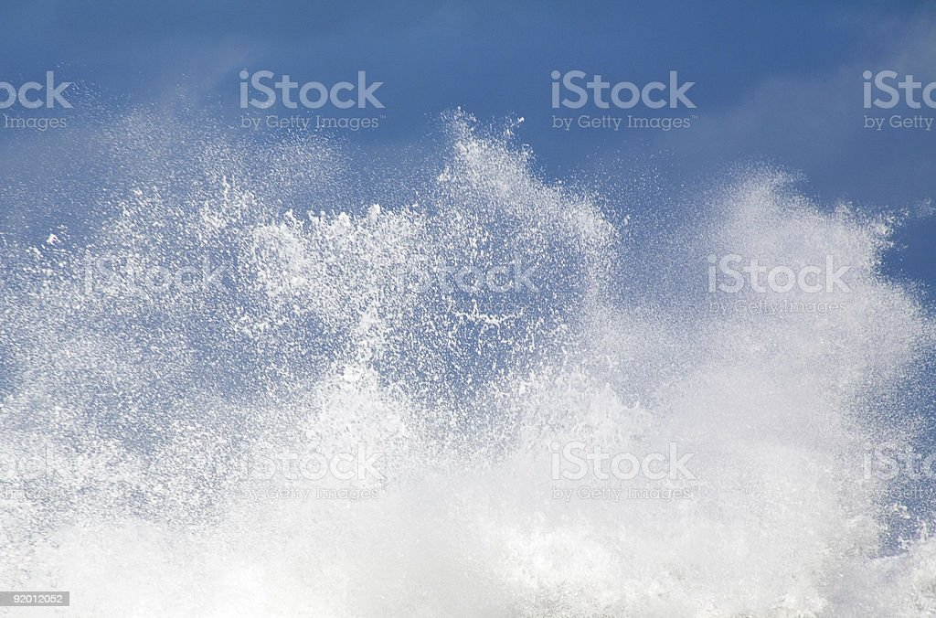 White wave crashing with a blue sky in background royalty-free stock photo