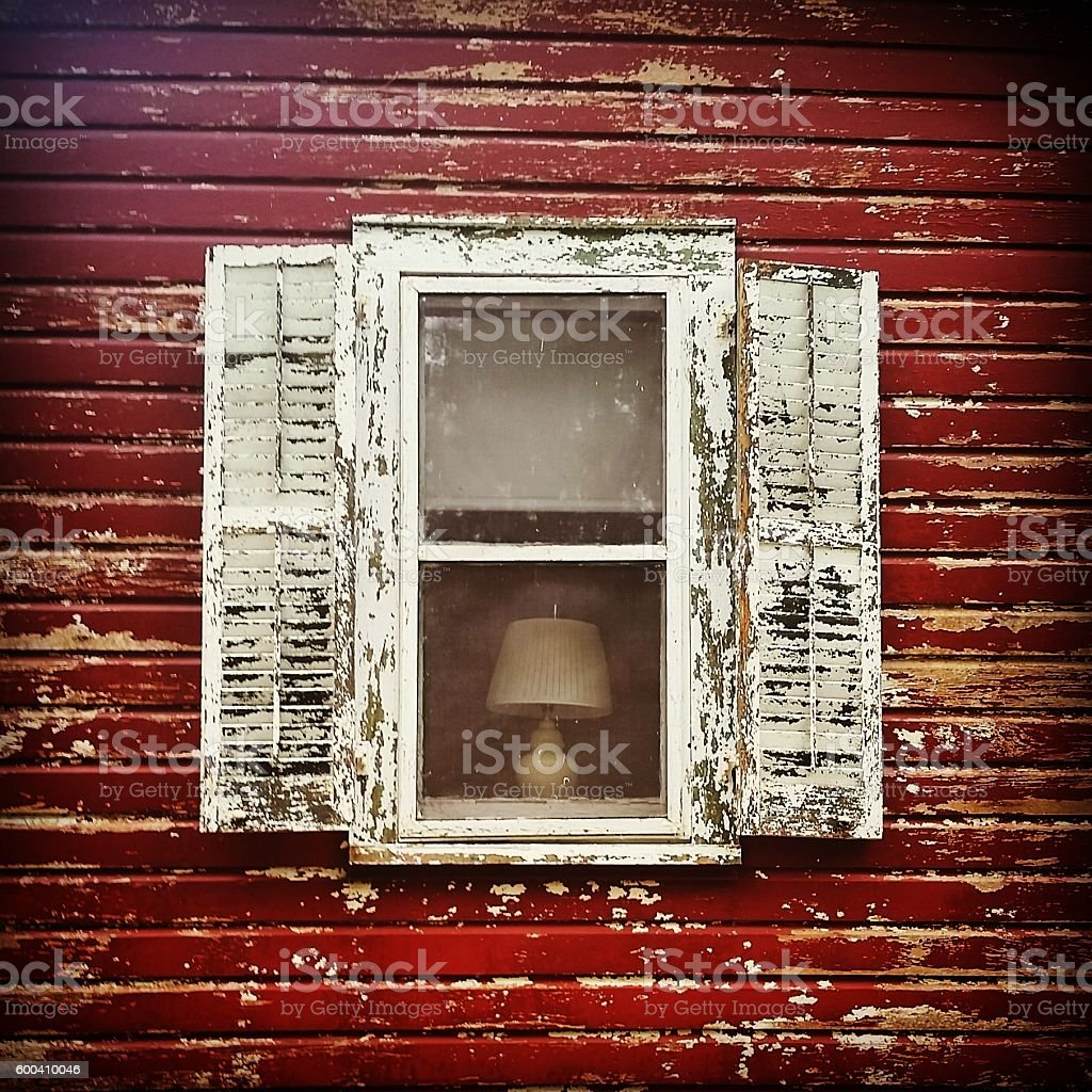 White Weathered Wooden Clapboard Shutters Open on Red Exterior Wall stock photo
