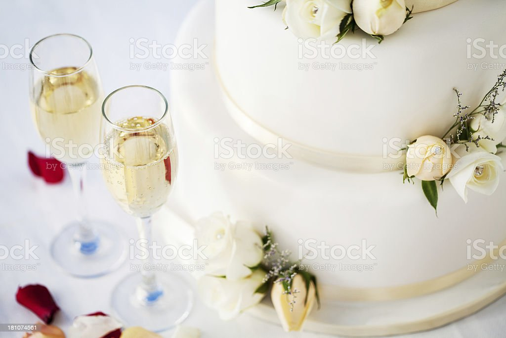 White Wedding Cake And Champagne Flutes On Table royalty-free stock photo
