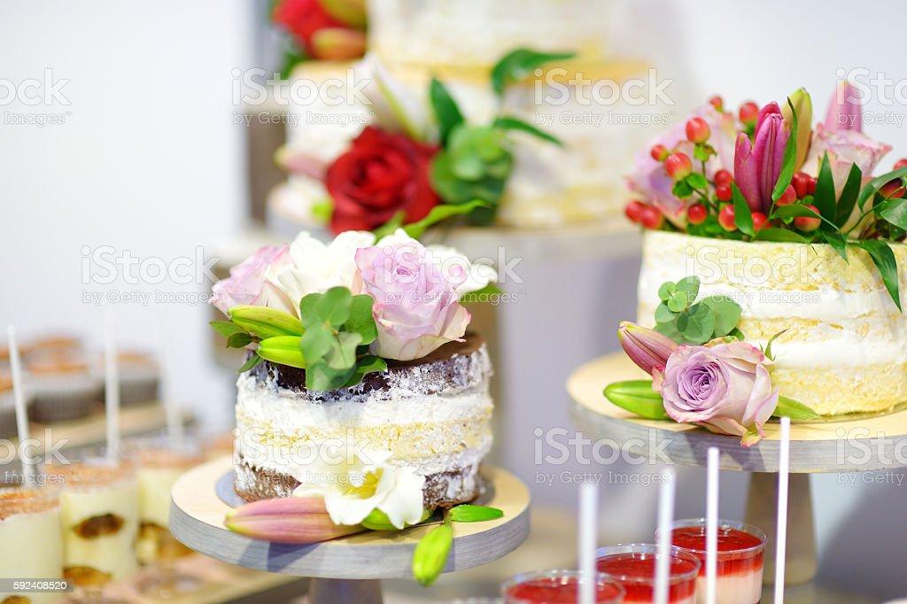 White wedding cake decorated with flowers stock photo