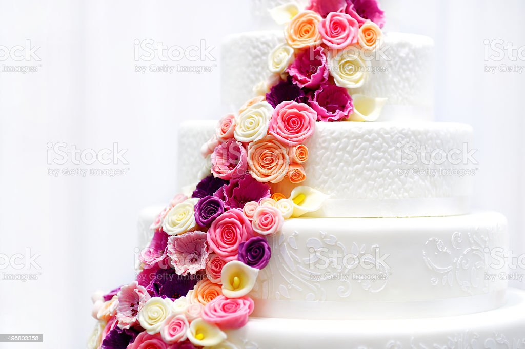 White wedding cake decorated with sugar flowers stock photo