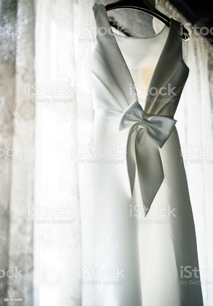 White Wedding Dress Hanging by the Window stock photo