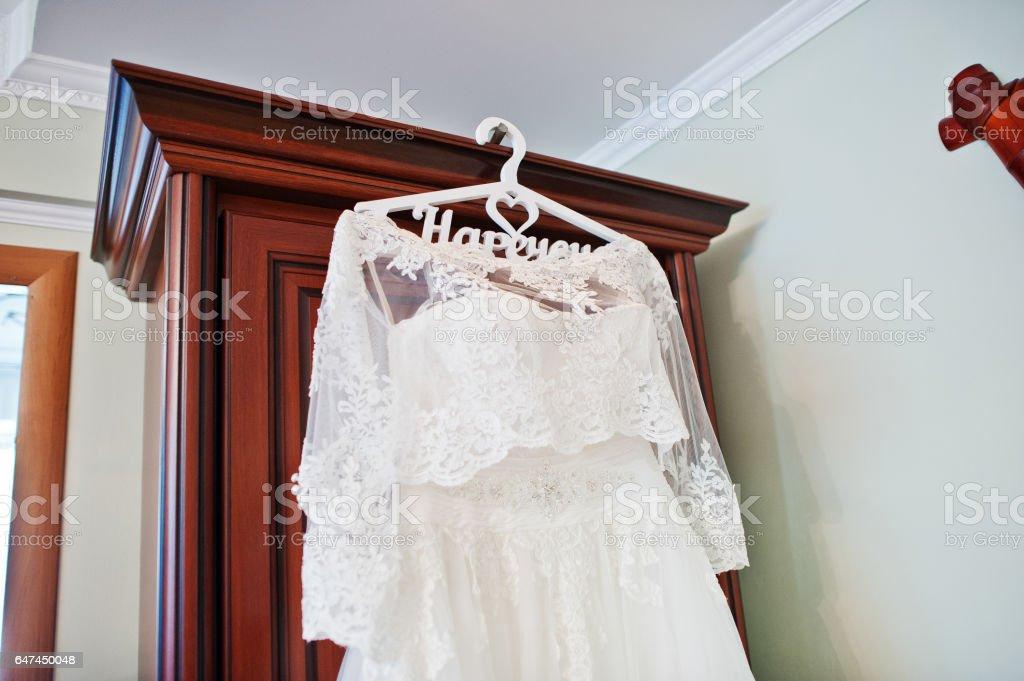 White wedding dress of bride on hangers at closet. stock photo