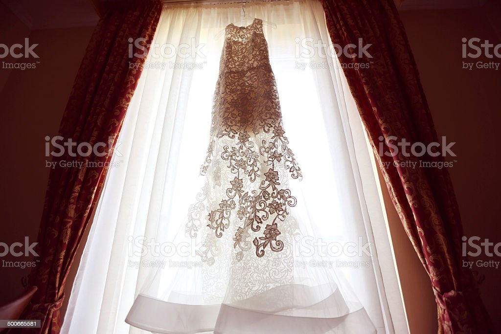 White Wedding dress on a shoulders, before ceremony sunny window stock photo