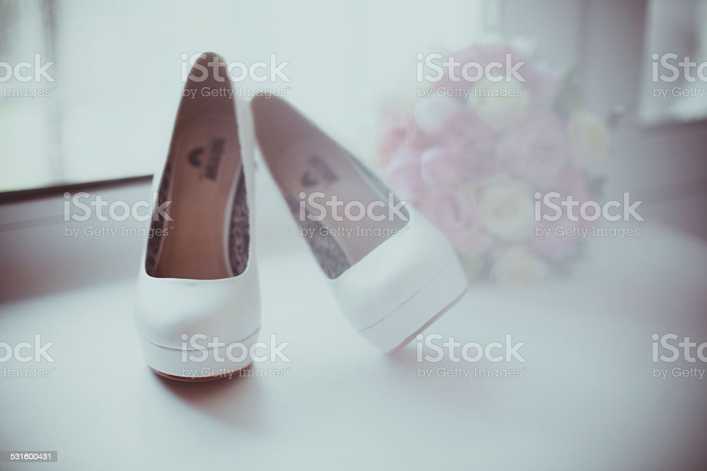 White wedding shoes bouquet on the window royalty-free stock photo