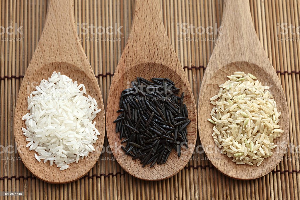 White, wild and brown rice in a wooden spoons royalty-free stock photo