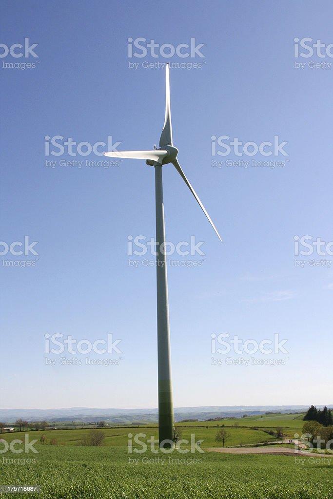 White wind turbine generating electricity on blue sky, Aveyron, France royalty-free stock photo