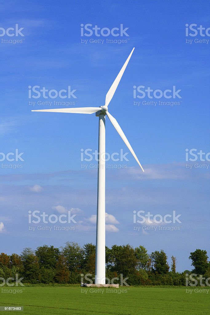 White wind turbine in a green field royalty-free stock photo