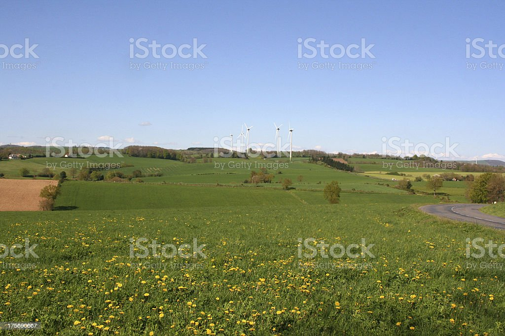 White wind turbines generating electricity on blue sky, Aveyron, France royalty-free stock photo