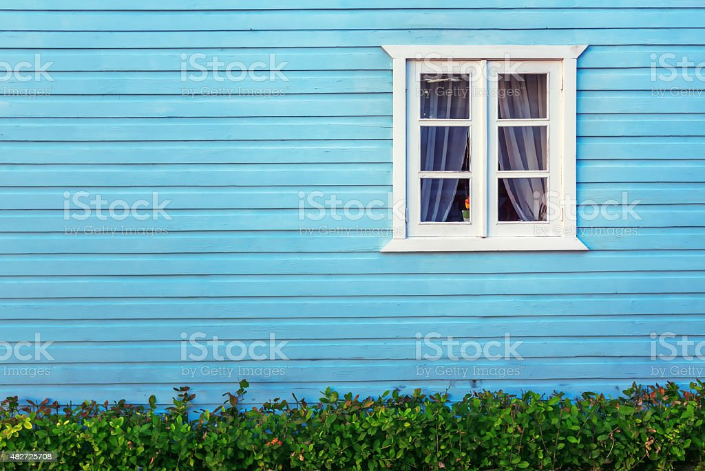 White window on a blue wooden wall in Dominican republic stock photo