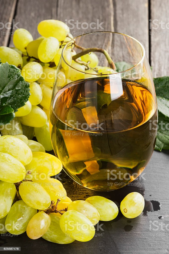 White wine and grapes on a dark background stock photo