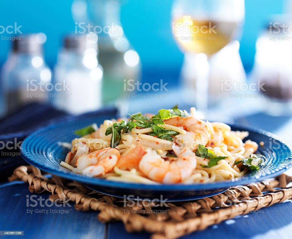 white wine and shrimp pasta with basil on blue plate stock photo