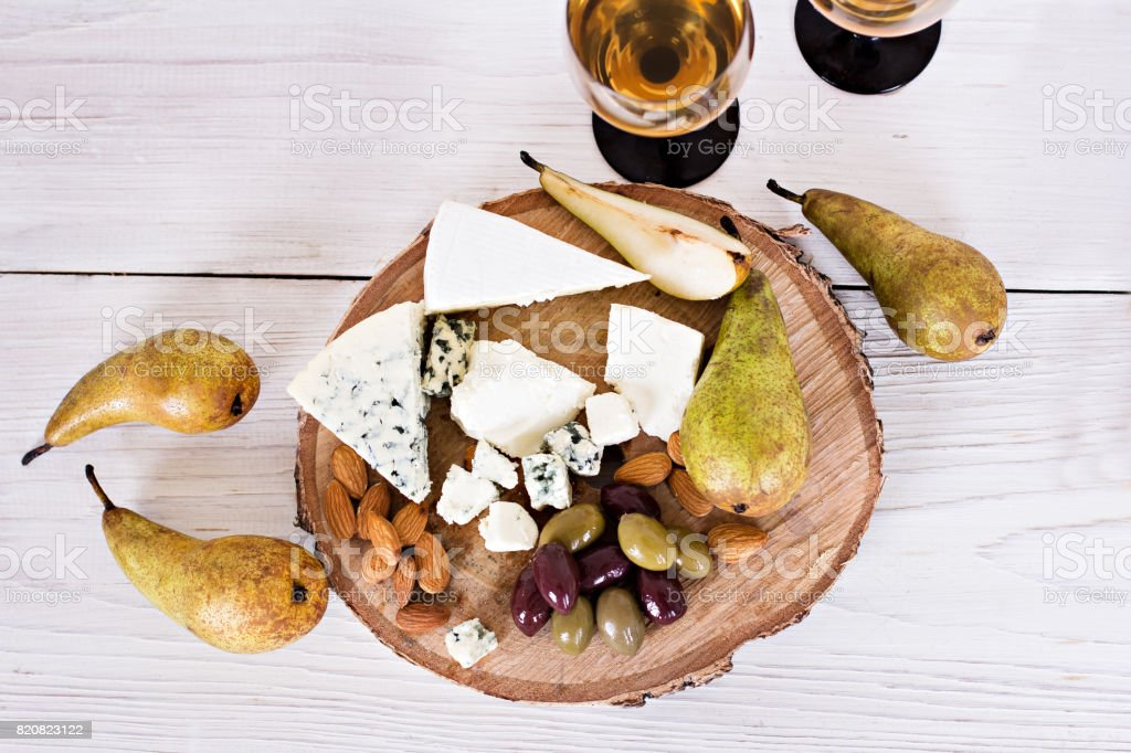White wine and snacks. Wine, grapes, cheese, nuts, olives. Romantic evening, still life. stock photo