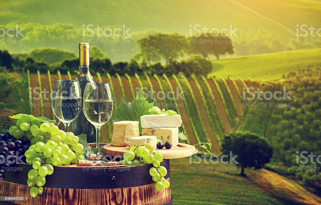 White wine bottle and  glass on wodden barrel. stock photo