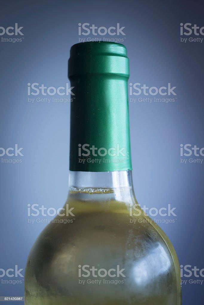 White wine bottle studio isolated close-up plain blue background stock photo