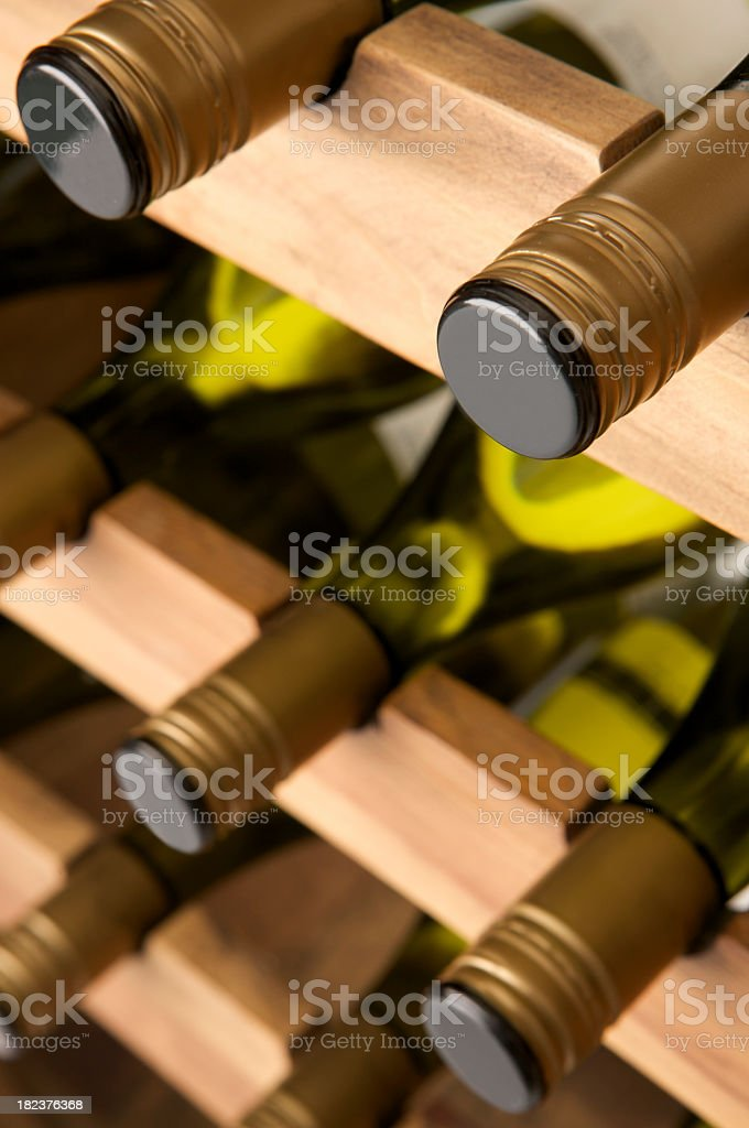 White wine bottles laid down in a large wooden rack. royalty-free stock photo