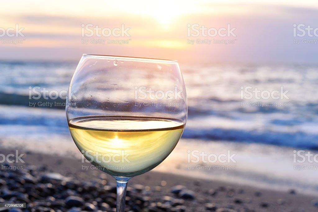 White wine filled glass on the beach at a colorful sunset stock photo