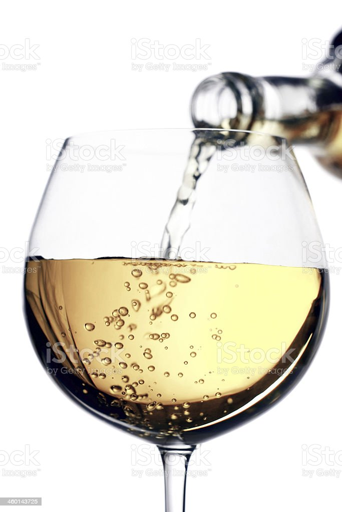 White wine pouring from a bottle to a glass stock photo
