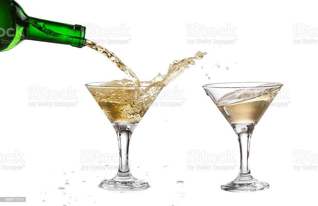 White wine pouring from the bottle intro the glass stock photo