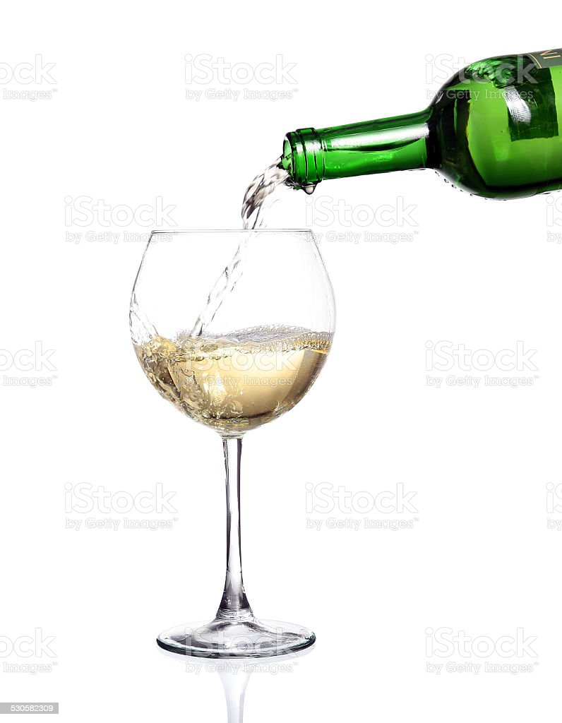 White wine pouring from the bottle stock photo