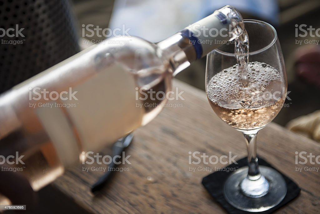 White wine pouring into glass stock photo