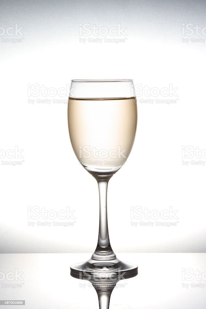 White wine pouring into wineglass on white background stock photo