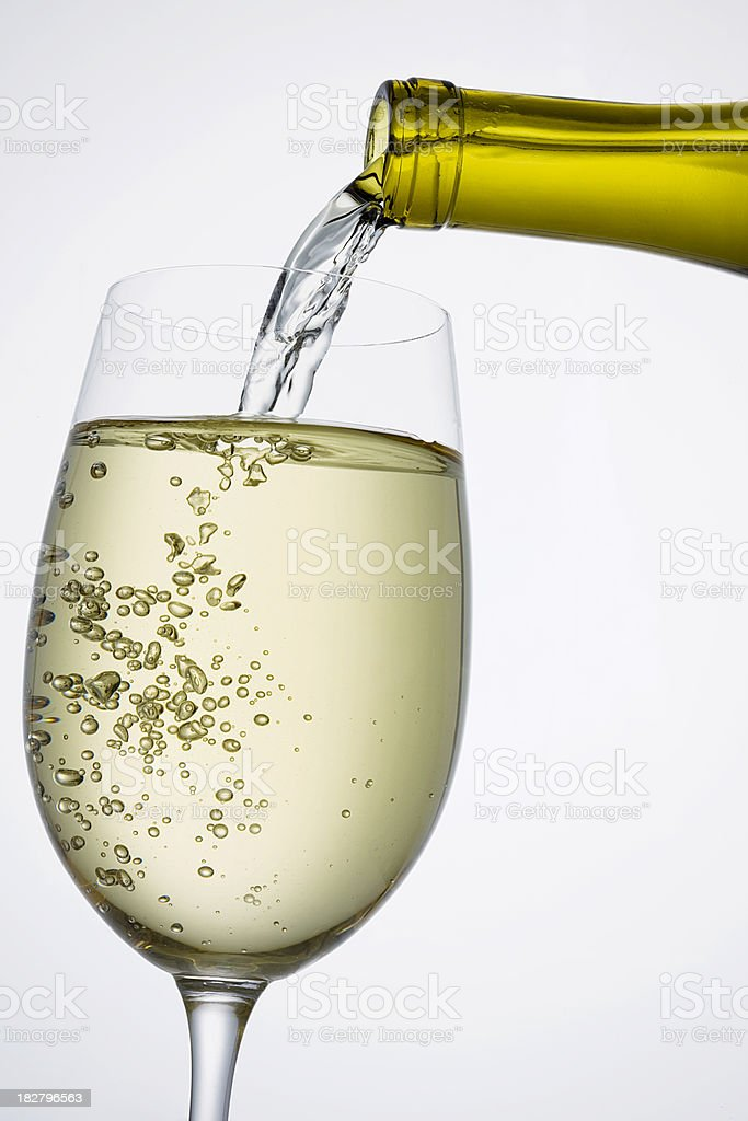 White wine pouring into wineglass royalty-free stock photo