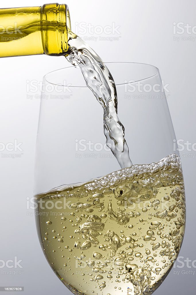 White wine pouring into wineglass royalty-free stock photo