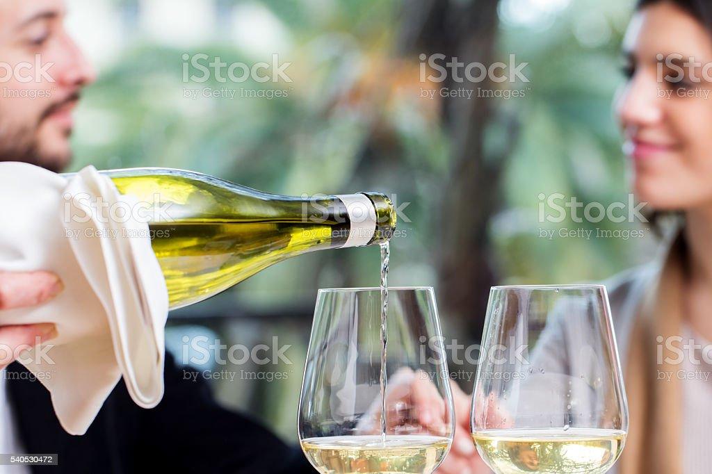 Vin blanc offerte avec couple en arrière-plan. photo libre de droits
