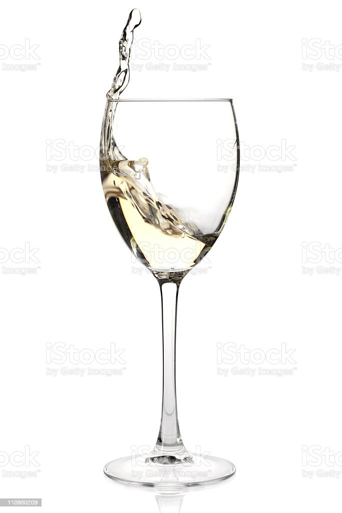 White wine splashing in a glass on white background stock photo