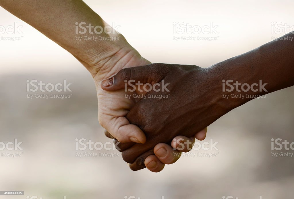 White Woman and African Girl Holding Hands Friendship Symbol stock photo