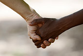 White Woman and African Girl Holding Hands Friendship Symbol