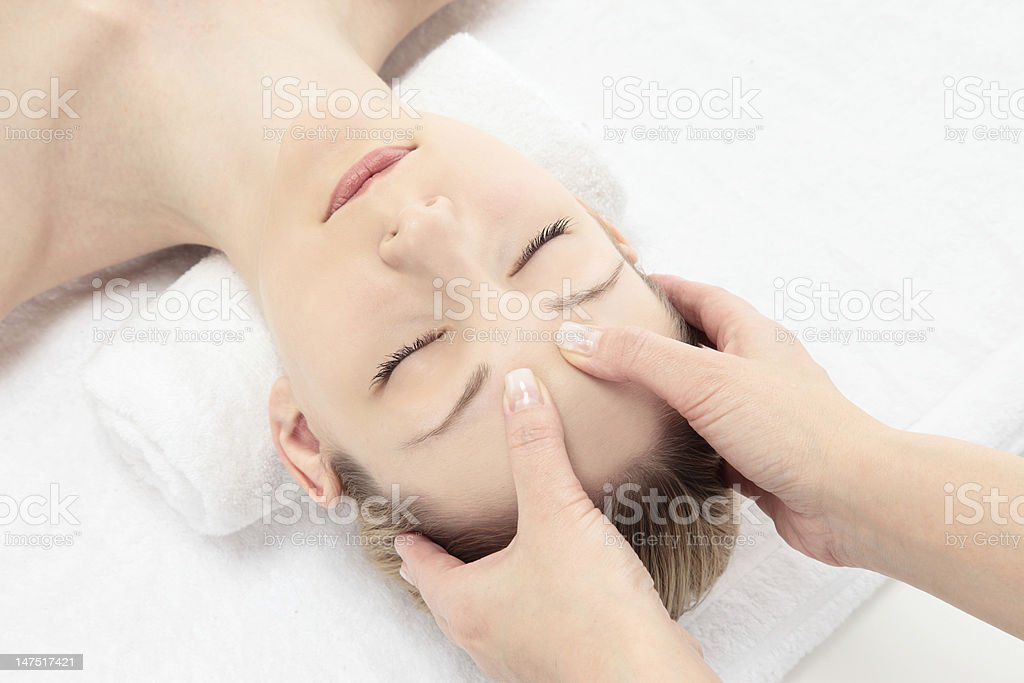 White woman receiving a facial massage on white towel stock photo