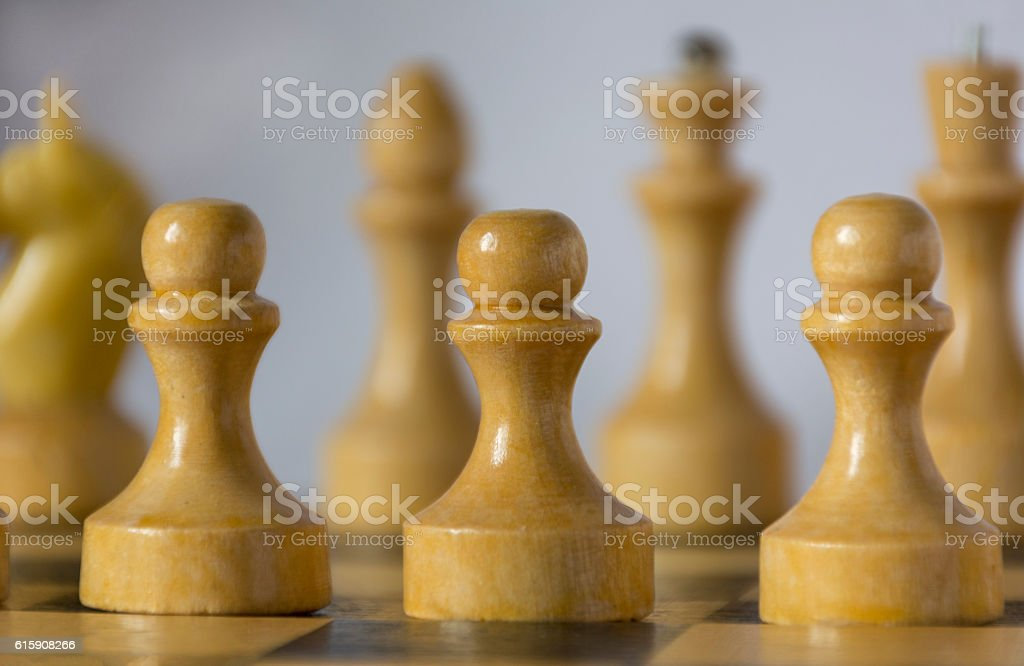 white wooden chessman, chess pieces stand on a chessboard stock photo