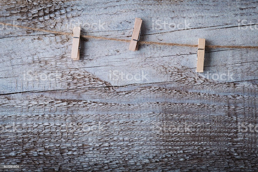 White wooden cloths pin hanging on rope over grunge wood stock photo
