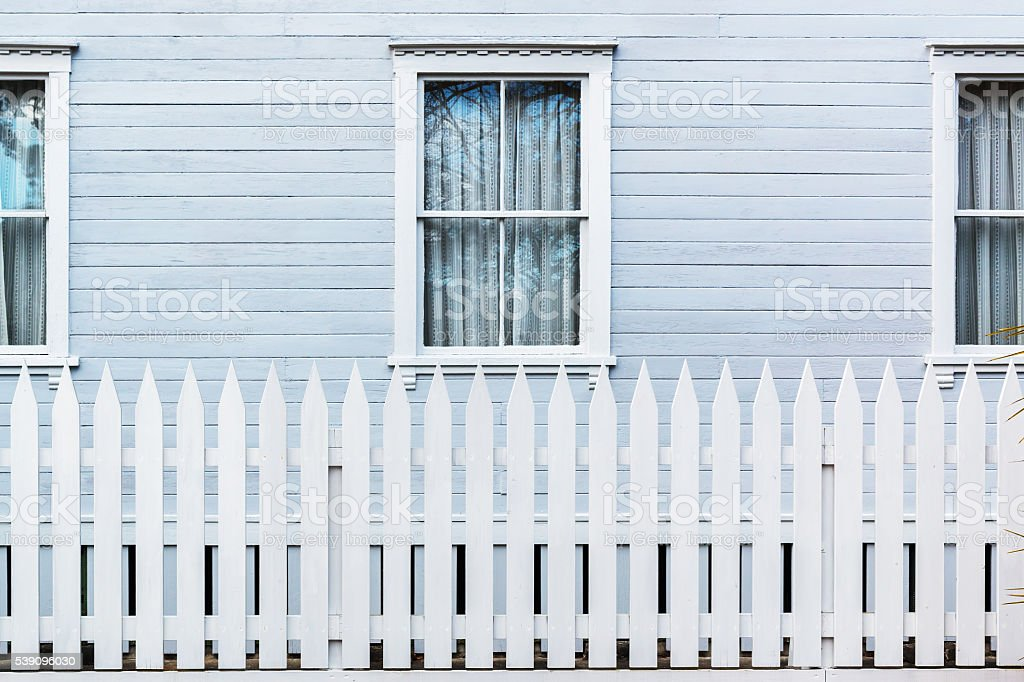 White wooden country style fence with windows of house stock photo
