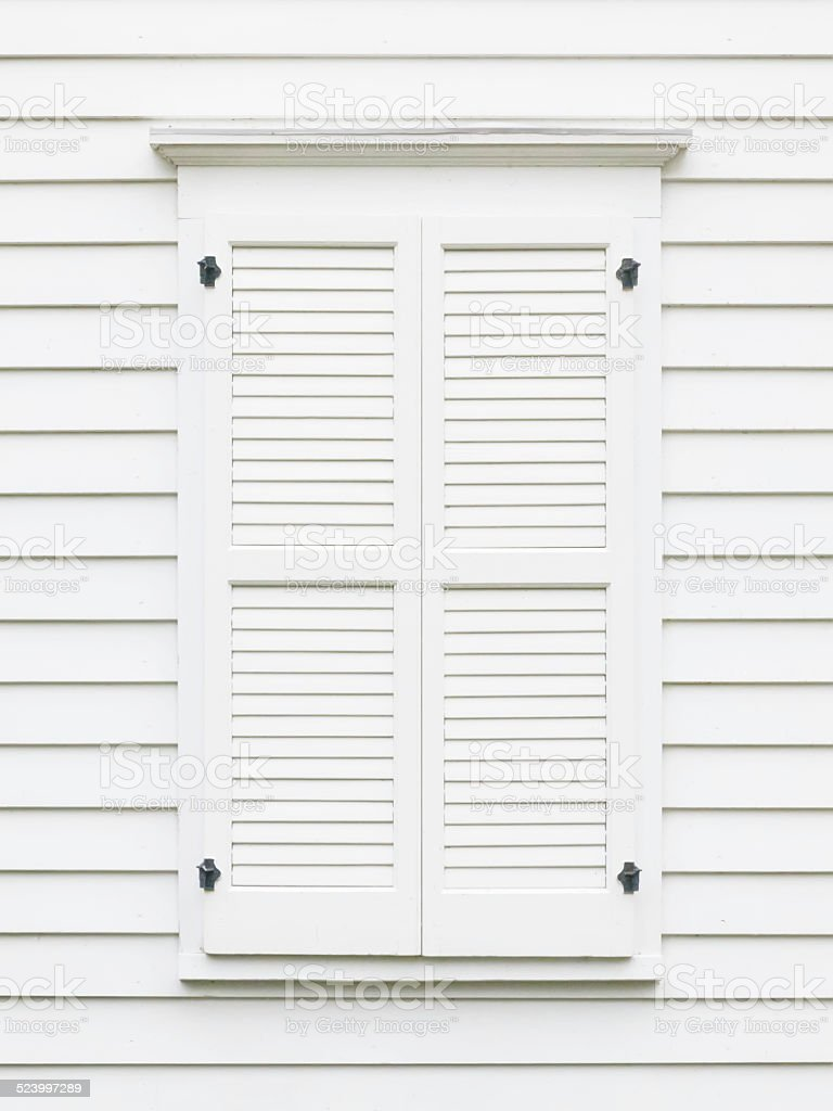 White wooden exterior window shutters on restored 19th-century house stock photo
