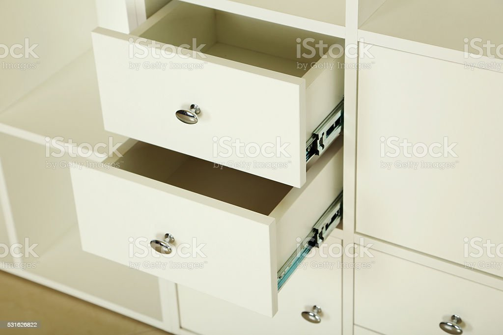 White wooden open boxes, white chest of drawers stock photo