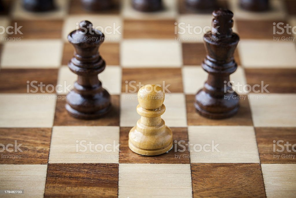 White wooden pawn between black king and queen royalty-free stock photo