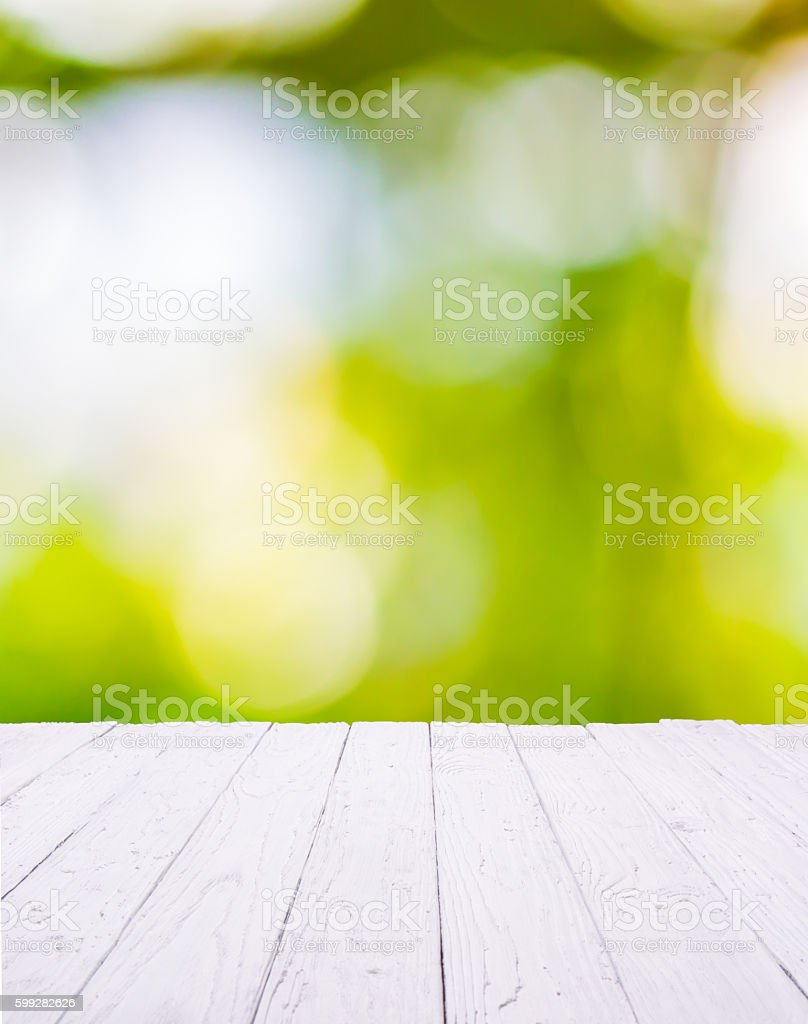 White wooden table with green bokeh background stock photo