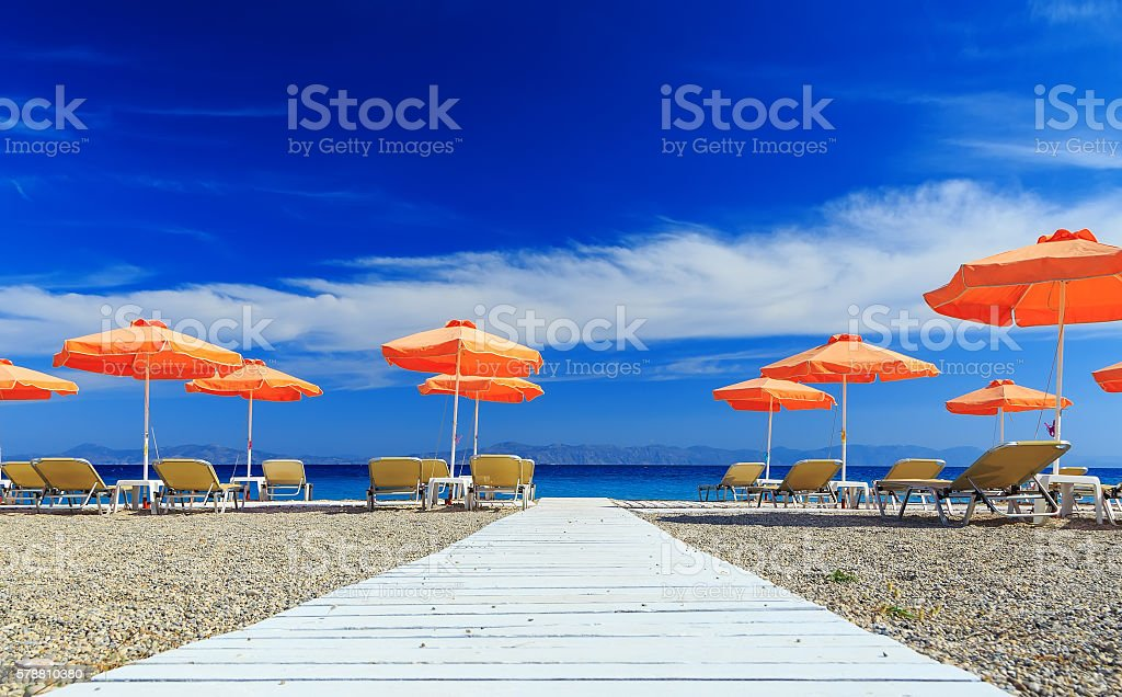 White wooden walkway leading to beach with umbrellas and sunbeds stock photo