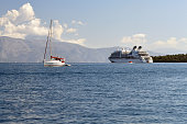 White yacht and big cruise ship in calm sea