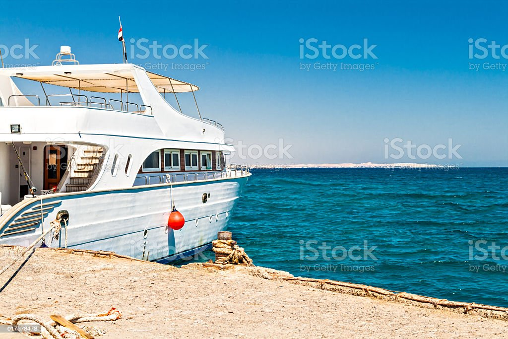 White yacht at the pier in the sea stock photo