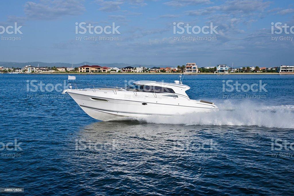 White yacht sailing across a coast stock photo