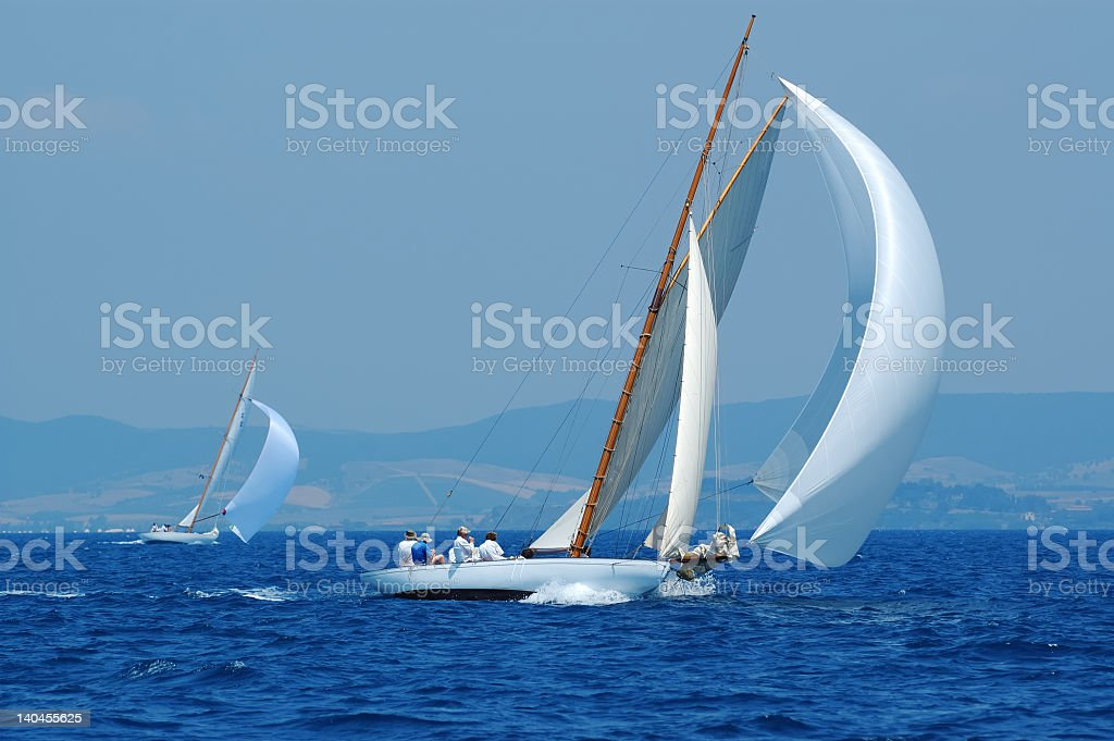 White yacht with large white sail stock photo