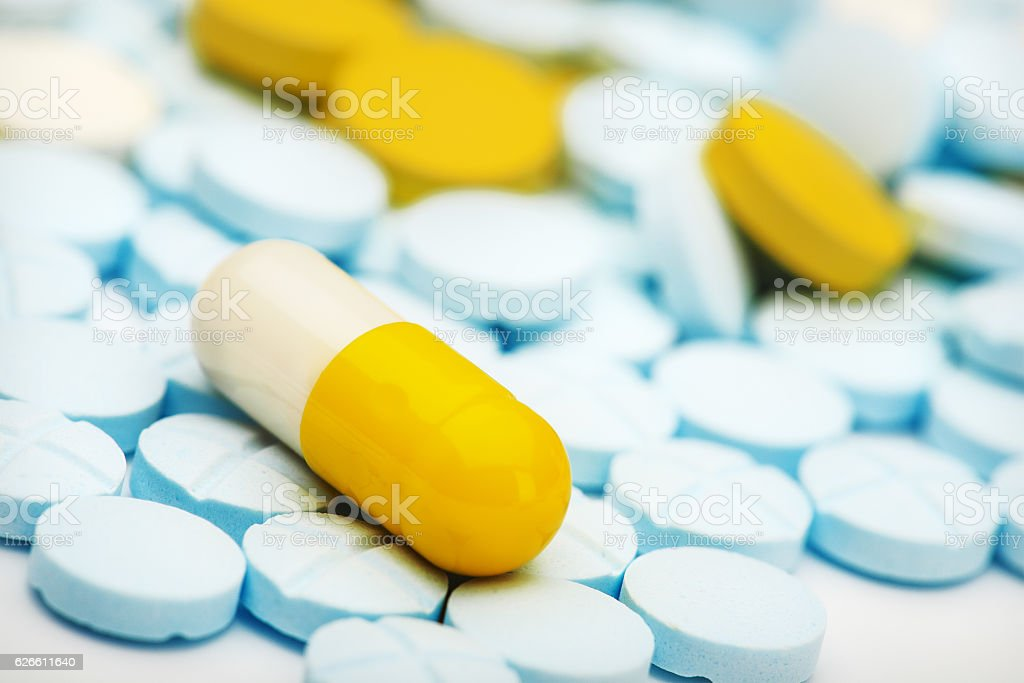 white yellow pill on a pile of medical pills stock photo
